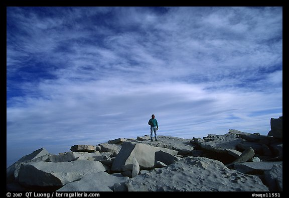 Hiker standing on flat rocks on top of Mt Whitney summit. Sequoia National Park, California (color)