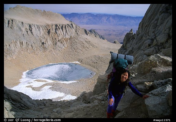 Woman with backpack pausing on steep terrain above Iceberg Lake. Sequoia National Park, California (color)