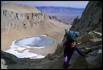 Woman with backpack pausing on steep terrain above Iceberg Lake. Sequoia National Park, California