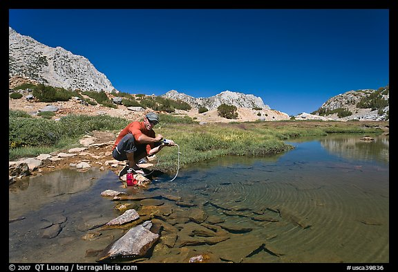 Man filtering water from stream, John Muir Wilderness. Kings Canyon National Park, California (color)