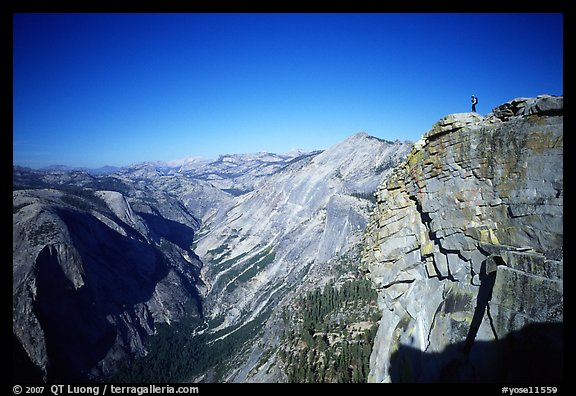 Hiker standing on top of Half-Dome, overlooking Tenaya Canyon. Yosemite National Park, California (color)