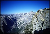 Hiker standing on top of Half-Dome, overlooking Tenaya Canyon. Yosemite National Park, California