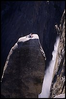 Climber resting on top of Lost Arrow spire with Yosemite Falls behind. Yosemite National Park, California
