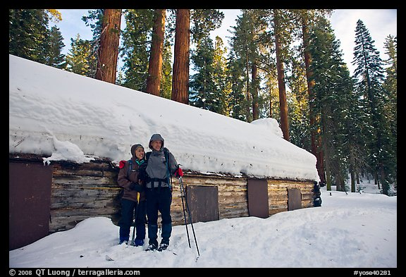 Skiing couple in front of the Mariposa Grove Museum in winter. Yosemite National Park, California