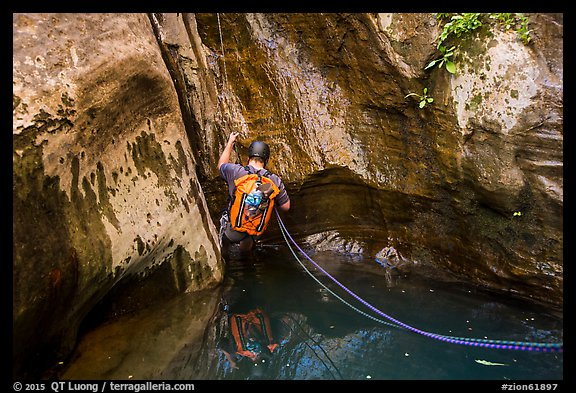 Canyoneer rappels into pool of water, Mystery Canyon. Zion National Park, Utah (color)