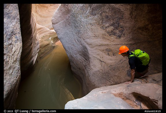 Canyoneer looks at water-filled pool. Zion National Park, Utah (color)