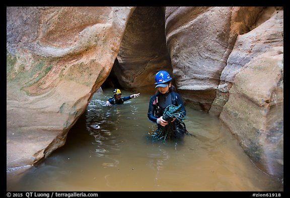 Woman carries rope, as man wades in chest-high water in Pine Creek Canyon. Zion National Park, Utah (color)