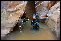 Woman carries rope, as man wades in chest-high water in Pine Creek Canyon. Zion National Park, Utah ( color)