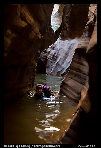 Woman in deep water of dark narrows, Pine Creek Canyon. Zion National Park, Utah (color)