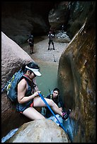 Canyoneer lowers herself using rope, Orderville Canyon. Zion National Park, Utah ( color)