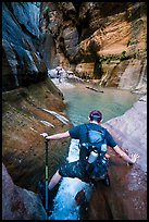 Hiker straddling stream in Orderville Canyon. Zion National Park, Utah ( color)
