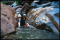 Woman walking in stream, Orderville Canyon. Zion National Park, Utah ( color)