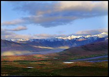 Tarn lakes, tundra, and snowy mountains of Alaska Range with patches of light. Denali National Park, Alaska, USA.