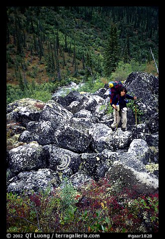 Backpacker on boulder field in Arrigetch Creek. Gates of the Arctic National Park, Alaska