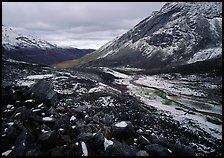 Boulders, valleys and slopes with fresh snow in cloudy weather. Gates of the Arctic National Park, Alaska, USA.