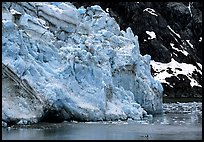 Kayaker dwarfed by Lamplugh glacier. Glacier Bay National Park, Alaska, USA.