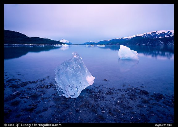 Beached translucent iceberg and Muir inlet at dawn. Glacier Bay National Park, Alaska, USA.