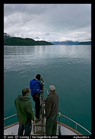 Film crew working on the bow of a small boat. Glacier Bay National Park (color)