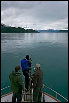 Film crew working on the bow of a small boat. Glacier Bay National Park, Alaska, USA. (color)