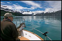 Man sitting at the bow of a small boat. Glacier Bay National Park, Alaska, USA.