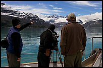 Crew filming from the deck of a boat. Glacier Bay National Park, Alaska, USA. (color)