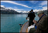 Film producer taking notes as crew films. Glacier Bay National Park, Alaska, USA. (color)