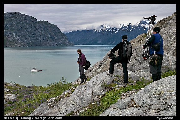 Film crew carrying a motion picture camera down rocky slopes. Glacier Bay National Park (color)