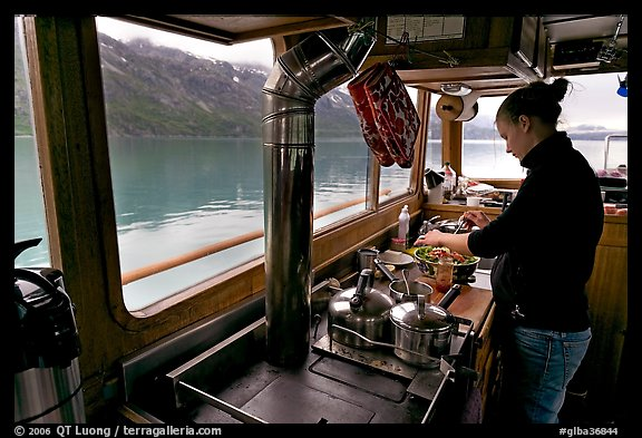 Chef preparing sadad in the main cabin of the Kahsteen. Glacier Bay National Park, Alaska, USA.