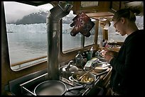 Woman preparing a breakfast aboard small tour boat. Glacier Bay National Park, Alaska, USA. (color)