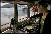 Woman cooking eggs aboard small tour boat, with glacier in view. Glacier Bay National Park, Alaska, USA.