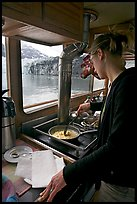 Woman cooking eggs aboard small tour boat, with glacier outside. Glacier Bay National Park, Alaska, USA.