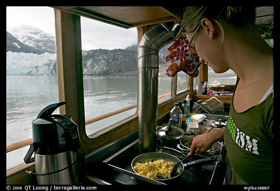Woman prepares breakfast eggs aboard small tour boat, with glacier in view. Glacier Bay National Park, Alaska, USA.