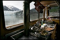 Breakfast potatoes in a small boat moored in front of glacier. Glacier Bay National Park, Alaska, USA. (color)