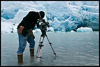 Cameraman standing in water at the base of Reid Glacier. Glacier Bay National Park, Alaska, USA. (color)