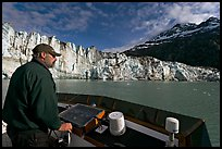 Captain guiding boat near Lamplugh glacier. Glacier Bay National Park, Alaska, USA.