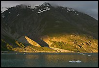 Sunset light falling on the base of the peaks around Tarr Inlet. Glacier Bay National Park, Alaska, USA.