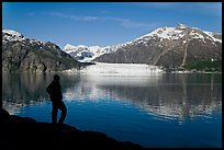 Man in silhouette looking at Tarr Inlet, Fairweather range and Margerie Glacier. Glacier Bay National Park, Alaska, USA.