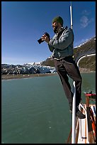 Photographer perched on boat in Reid Inlet. Glacier Bay National Park, Alaska, USA. (color)