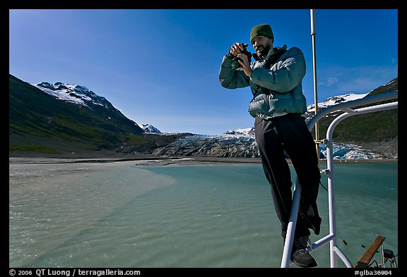 Photographer perched on boat with Reid Glacier behind. Glacier Bay National Park (color)