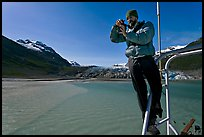 Photographer perched on boat with Reid Glacier behind. Glacier Bay National Park, Alaska, USA. (color)