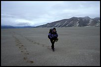 Backpacker hikes in sand-like ash, Valley of Ten Thousand smokes. Katmai National Park, Alaska
