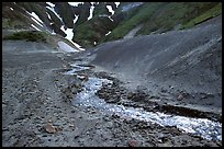 Stream flows from verdant hills into  barren valley floor. Katmai National Park, Alaska, USA.