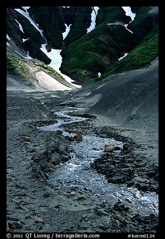 Stream flows from the verdant hills into the barren floor of the Valley of Ten Thousand smokes. Katmai National Park (color)