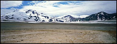 Snow-covered mountains surrounding ash-covered flats. Katmai National Park (Panoramic color)