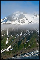 Glacier, and cloud hanging at mid-height of peak. Kenai Fjords National Park, Alaska, USA.