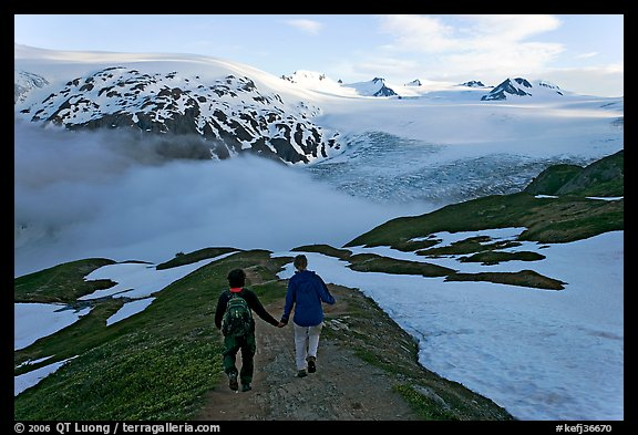 Couple hiking down Harding Icefied trail, late afternoon. Kenai Fjords National Park, Alaska, USA.