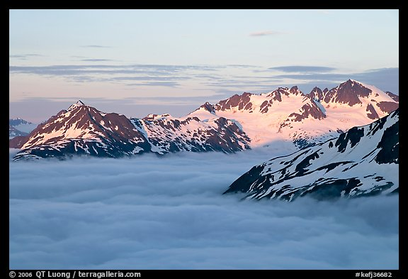 Midnight sunset on peaks above clouds. Kenai Fjords National Park, Alaska, USA.