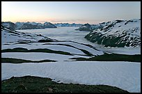Bands freshly uncovered by snow, and low clouds, sunrise. Kenai Fjords National Park, Alaska, USA.