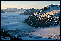 Craggy peaks, glacier, and sea of clouds. Kenai Fjords National Park, Alaska, USA.