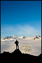 Hiker standing on overlook above Harding icefield. Kenai Fjords National Park, Alaska, USA. (color)